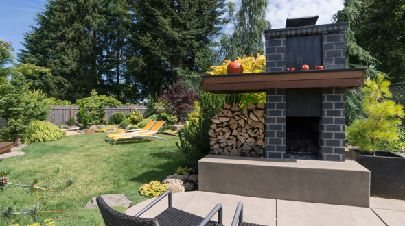 Backyard landscape with trees surrounding a fireplace