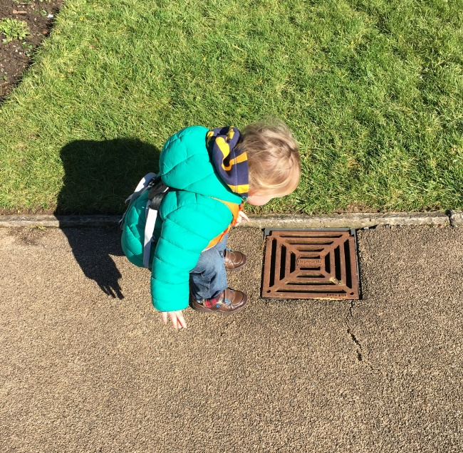 toddler crouched looking into small drain in the path