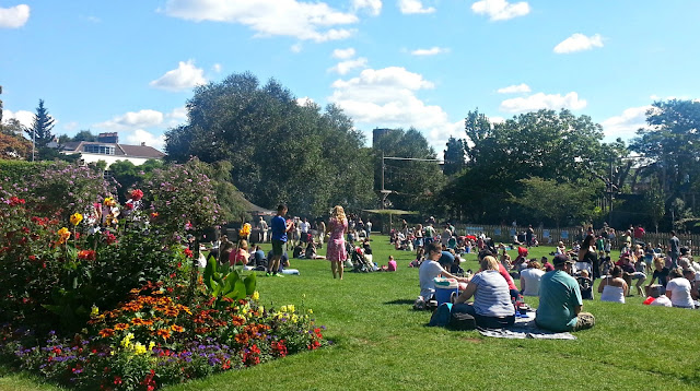 Flower lined green space with picnickers on the grass