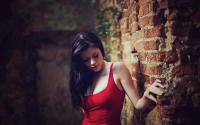 Linda chica de rojo apoyada sobre una pared