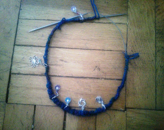 A set of cast on stitches on a long circular needle.  Stitch markers in a variety of shapes are placed along the needle.