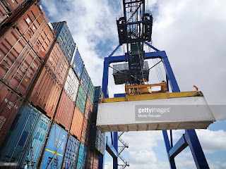 Shipping containers with gantry crane. (Credit: Cultura Creative (RF)/Alamy Stock Photo) Click to Enlarge.