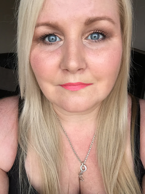 wearing the Maybelline Color Drama Lipstick in the shade in with coral