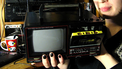 [Image: A person holding a portable television-cassette player measuring roughly 30 by 30 by 20 cm. The tape compartment is open and a yellow cassette is in. The device is labeled 'BLACK/WHITE TELEVISION-RADIO-CASSETTE PLAYER' with the brand name 'ACTION'. There's a cathode-ray type display roughly 20cm across; band selector for VHF low, VHF high, UHF, FM, and AM; A tuning wheel; a volume wheel; cassette control buttons on top; and a carrying handle. In the background, there's a bigger cassette deck, and a coffee cup with drawings of sheep.]