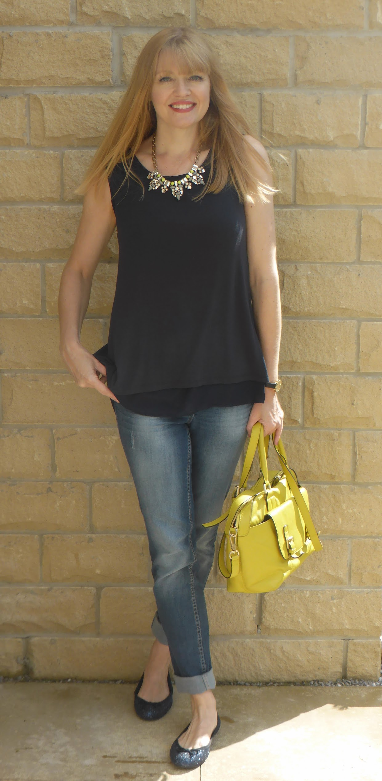 What Lizzy Loves wears navy top, distressed jeans and Happiness Boutique statement necklace.