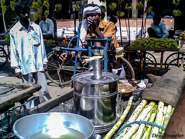 making sugarcane juice from a hand operated machine on a street of India