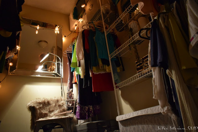 A small 8 x 6 closet space makeover using velvet hangers, upholstered storage boxes,Edison bulb light strands, armed chair and faux fur area rug.