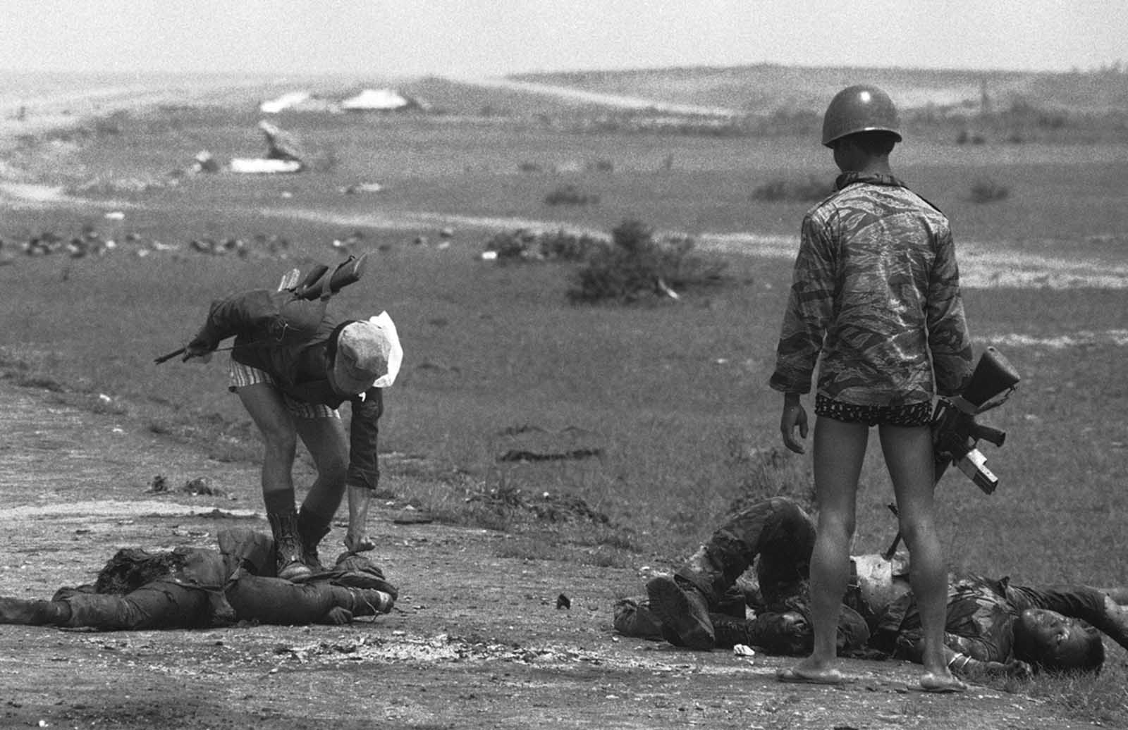 South Vietnamese Marines check the bodies of dead soldiers for cigarettes near My Chanh, new government defense line 20 miles north of Hue, on May 5, 1972. The soldiers were killed during fighting when Quang Tri City was abandoned.