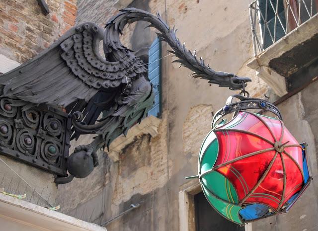 Marforio, an iron dragon and three glass umbrellas, Venice