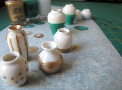 Selection of white dolls' house vases decorated with nail varnish.