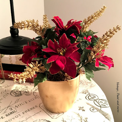 gold spray painted flower pot with faux berries, twigs and flowers