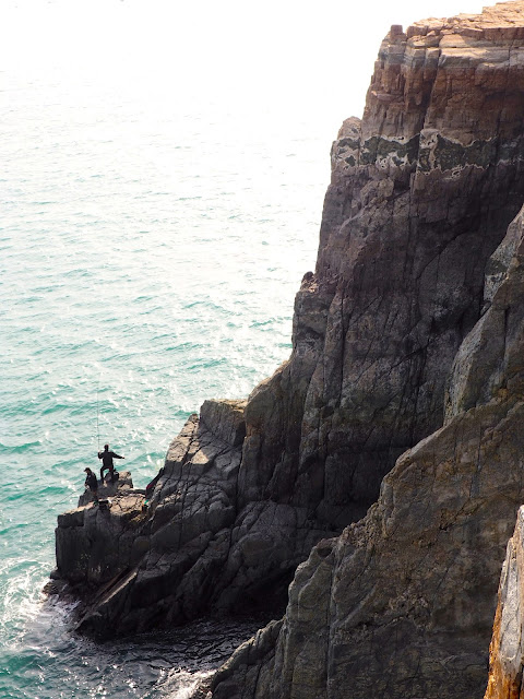 Fishing from the cliff side below Sinseon Rock, Taejongdae Park, Busan, South Korea