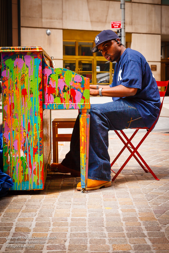 a photo of a man playing a brightly colored piano in new york city