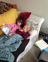 Siblings reading together on couch