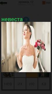 около окна стоит невеста в белом платье и с букетом цветов