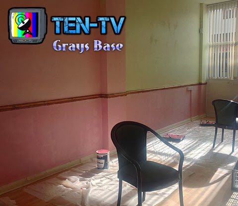 A big partially painted pink wall, with two big green chairs in the middle by a pot of paint. The text reads TEN-TV Grays Base.