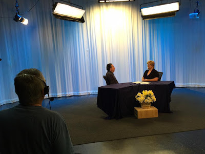 Nathan Romo and Darcie Elliott (right) sit and chat before recording Blindside Fresno starts. The backdrop is a white curtain lighted with blue light, there is a desk and a vase of flowers in the foreground.