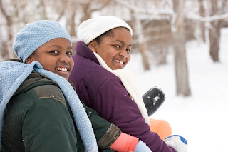 Two females sitting in snow looking at camera.