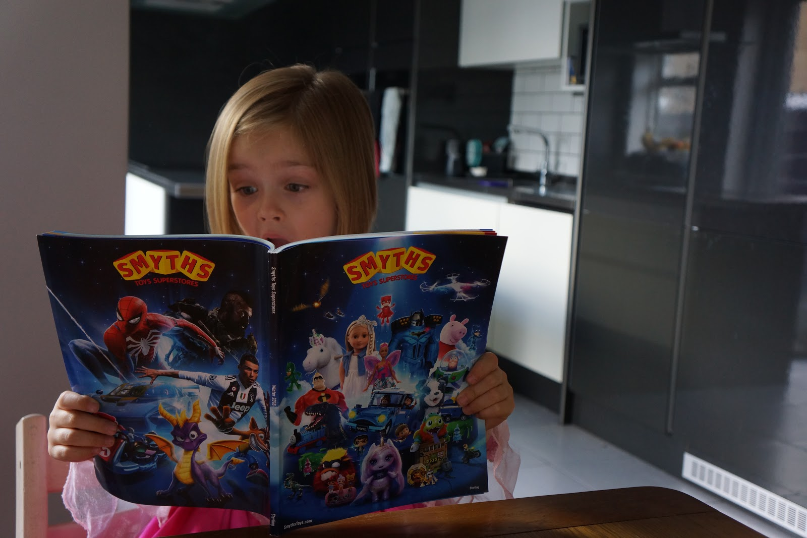 girl reading a toy catalogue