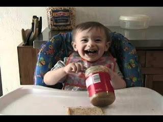 طفل صغير يتناول من زجاجة الفول السوداني بيديه
