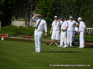 Young bowler shading eyes whilst looking towards the jack