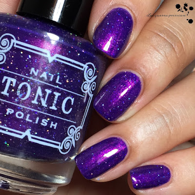 swatch of huckleberry sparkle by tonic nail polish which is a purple polish with red shimmer and large scattered holo