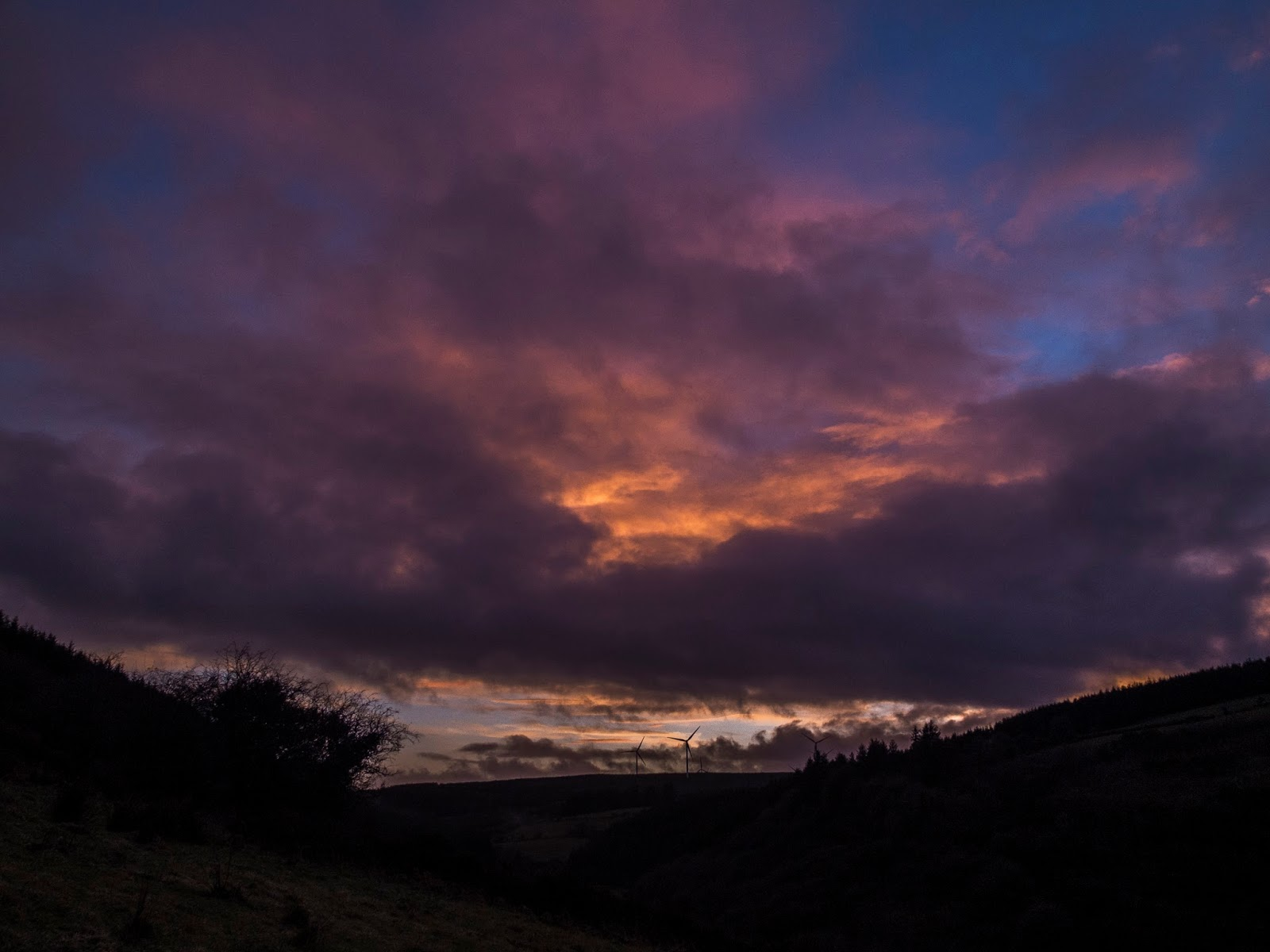 Sun setting over a valley in North Cork, Ireland with dramatic purple and pink clouds.