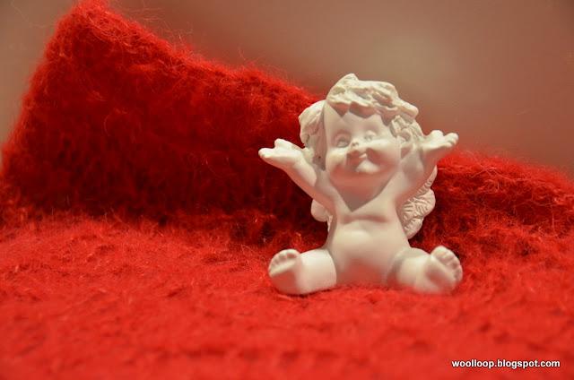 Gipsowy wesoły biały aniołek siedzący na ażurowym ręcznie dzierganym, czerwonym kominie