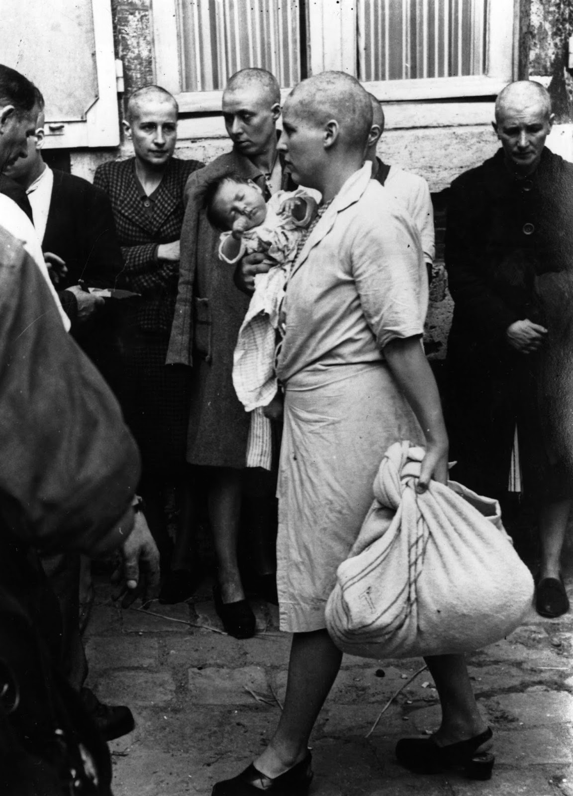A woman collaborator and her baby, whose father is German, returns to her home after having her head shaven following the capture of Chartres by the Allies.