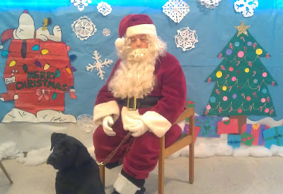 Santa sits in his red suit trimmed with white fur, beside him is guide dog Leif, a black Labrador, behind them we see a winter scne of snow flakes and houses.