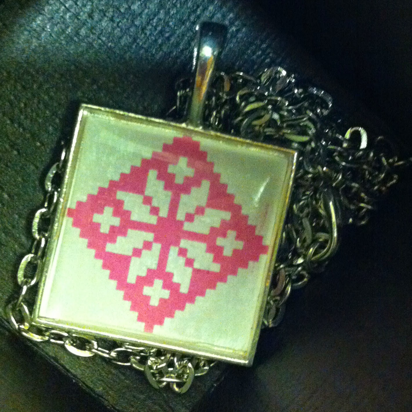 a pendant with a geometric pattern in a box