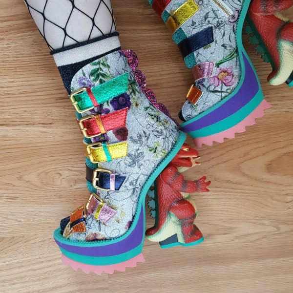 rubber soled platform boots with multiple straps and dinosaur heels worn on foot