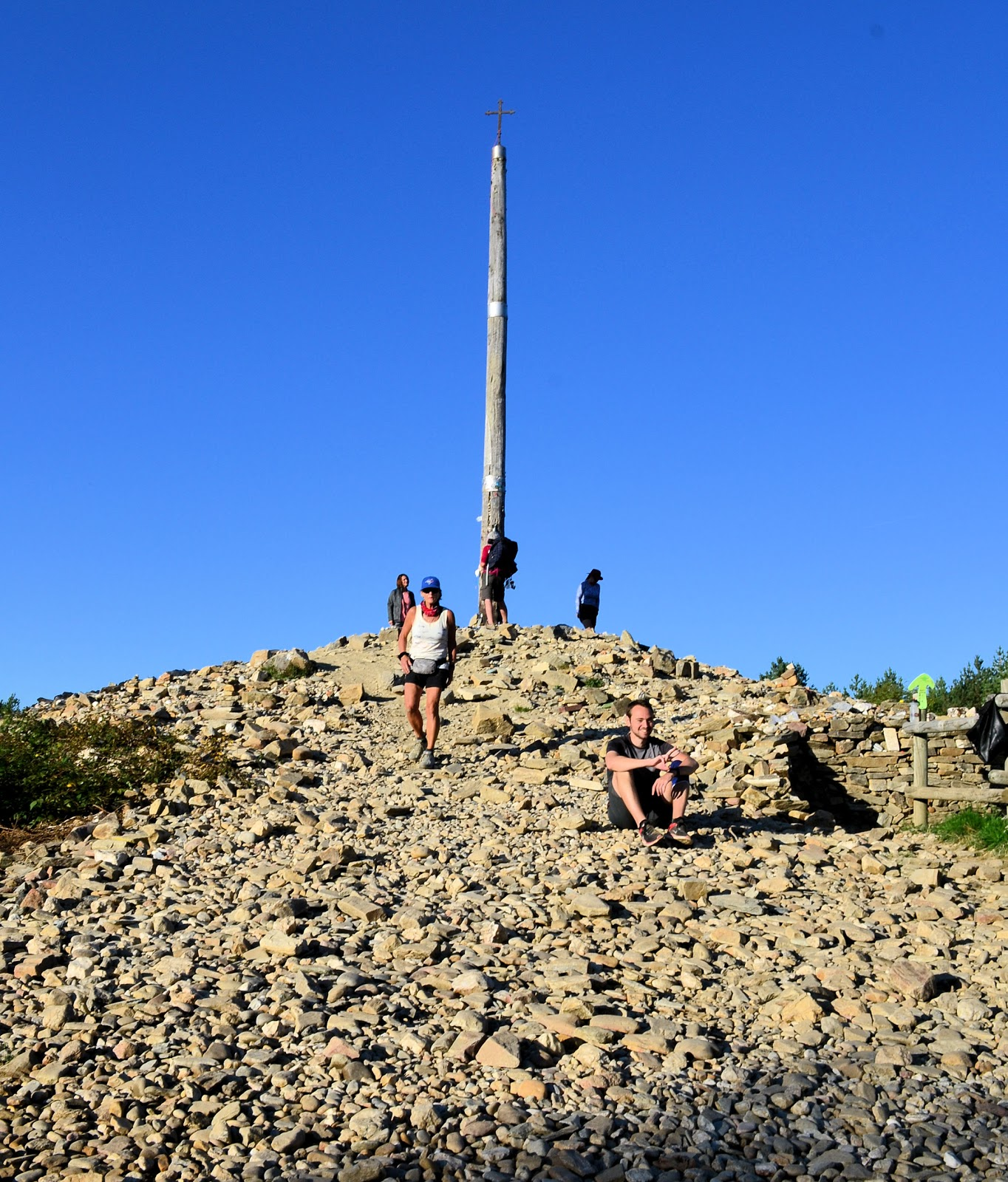 "Here, upon this mound of rocks with a weathered pole topped by an iron cross, pilgrims pray and toss their symbolic ""burdens"" of stone."