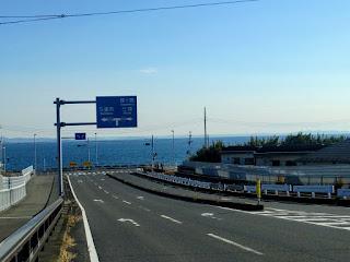 二車線の下りさかの先に見える青い空と青い海