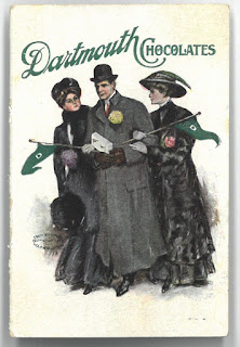 Image of Dartmouth Chocolate adversitement showing a well dressed man in an overcoat with a hat carrying a box of chocolates. There are two women, also well dressed clinging to his arm. Each woman holds a Dartmouth pennant.