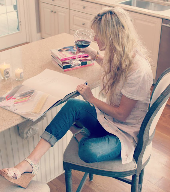 Michele of Hello Lovely reading book in white kitchen