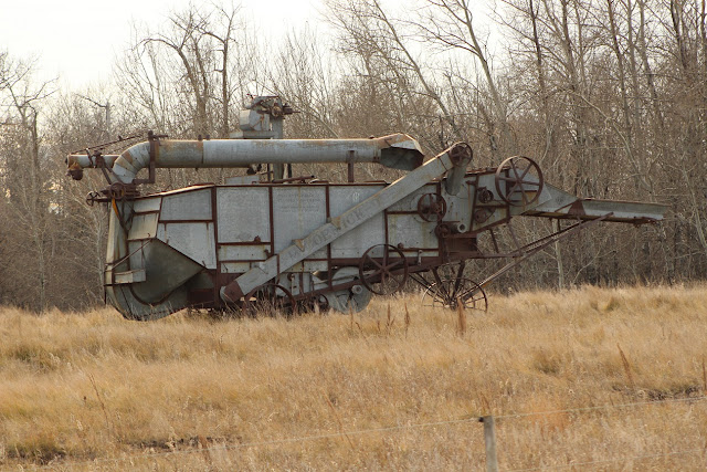 Old Threshing machine in grassy field