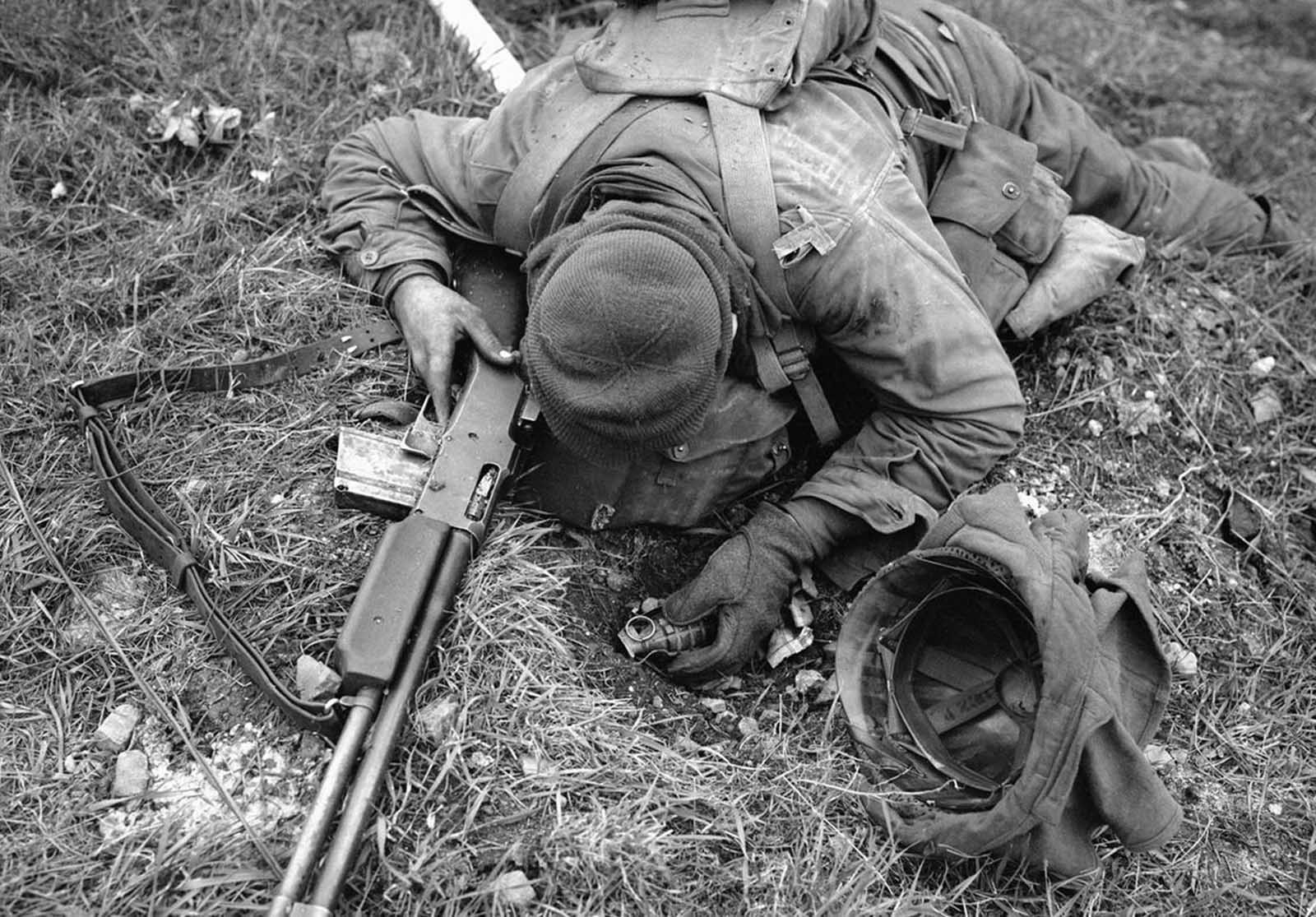 An unidentified American soldier, shot dead by a German sniper, clutches his rifle and hand grenade in March of 1945 in Coblenz, Germany.