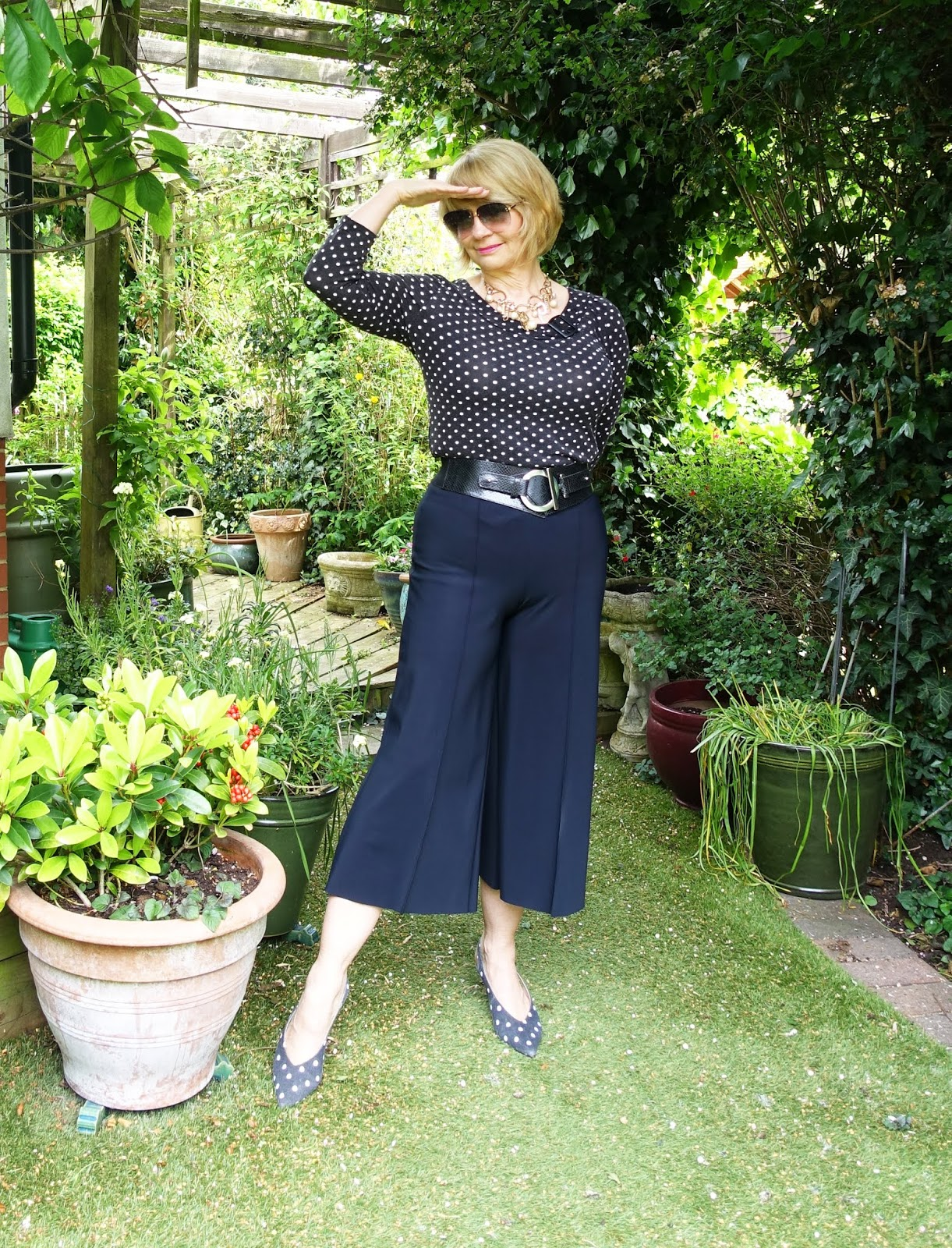 Mid life blogger in black cropped trousers, black and white polka dot top and matching sling back shoes