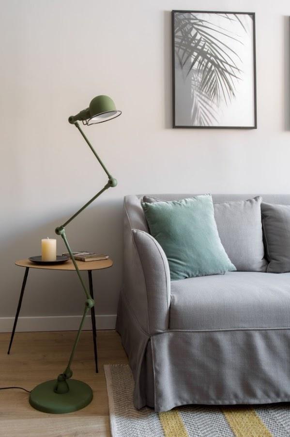 Detalle del salón con pared y sofá en gris, y mesita auxiliar