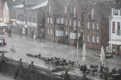 Lluvia torrencial en el muelle. Se ven mesas y sillas.