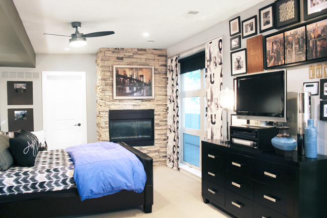 Master bedroom with stacked stone fireplace and blue bedding
