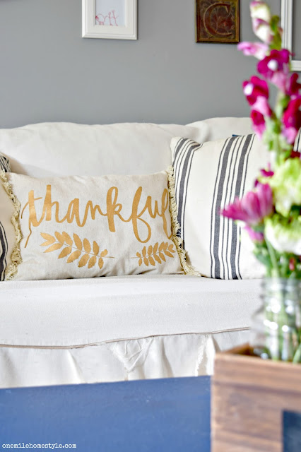 Gold and navy blue fall decor with farmhouse style pillows in the living room