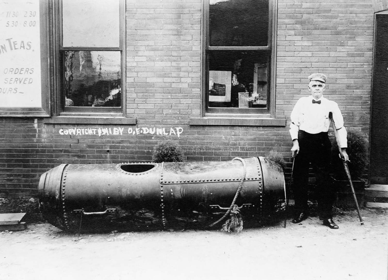 Bobby Leach, the second person to survive a trip over the falls, with the barrel he used to do it. 1911.