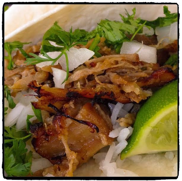 pork carnitas with onion cilantro and lime over a tortilla and rice