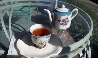 A floral tea pot, a non-matching tea cup with thin leaf blades and colored berries on it, and a white saucer all siting on a glass table outside.  Golden brown colored tea is in the cup.