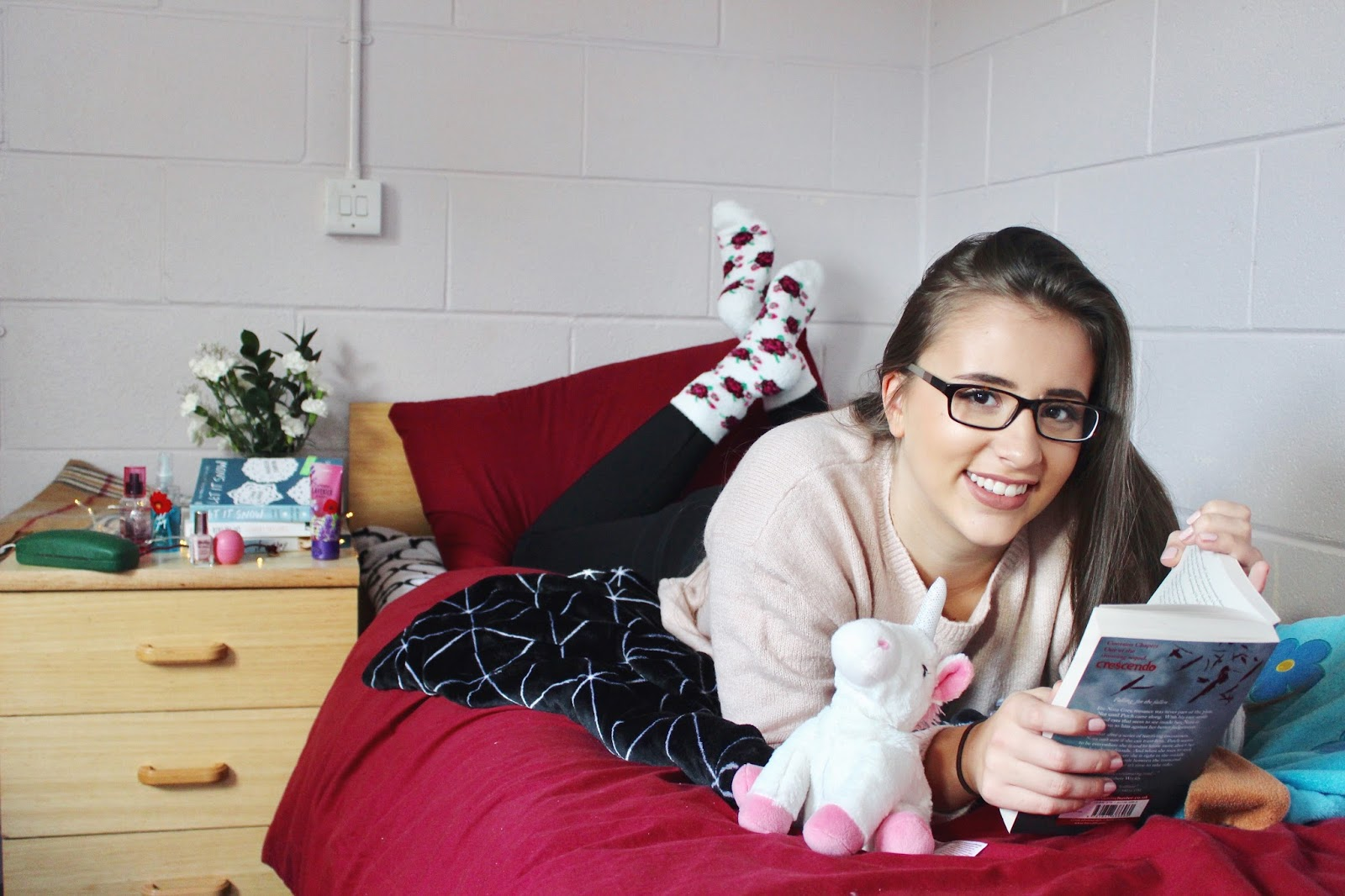 Girl laying on bed smiling and reading a book