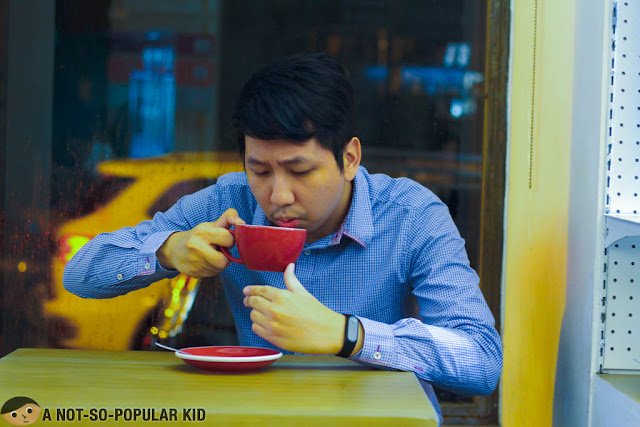 Renz Cheng sipping coffee in Yardstick Cafe