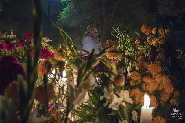 mujer rezando en panteon el dia de muertos