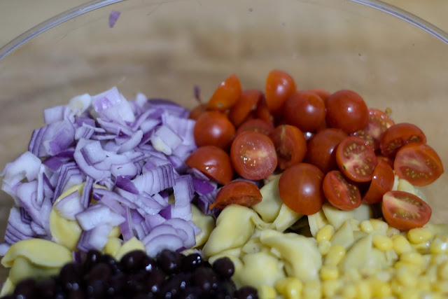 Diced red onion, cherry tomatoes, back beans, corn, and tortellini in a mixing bowl.